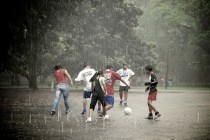 """Teenagers playing soccer in the rain"", de Marlon Dias"